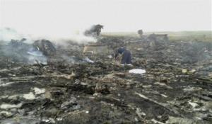 People walk amongst the debris at the crash site after a passenger plan was shot down Thursday as it flew over eastern Ukraine.