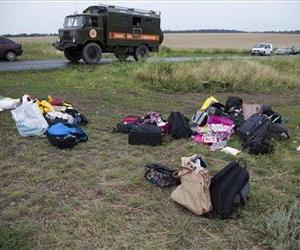 Passengers' personal luggage is collected at the site of a crashed Malaysia Airlines passenger plane near the village of Rozsypne, Ukraine, eastern Ukraine Friday, July 18, 2014.