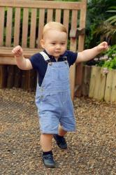 In this photo taken on Wednesday July 2, 2014,  to mark his first birthday, Britain's Prince George walks, during a visit to the Sensational Butterflies exhibition, at the Natural History Museum, London. The prince turns 1 on July 22.
