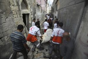 Palestinian medics carry a dead body found under the rubble of a home destroyed by an Israeli strike in the Shijaiyah neighborhood of Gaza City, northern Gaza Strip, Sunday, July 20, 2014. Hundreds of panicked residents have fled the neighborhood which they say has come under heavy tank fire from...