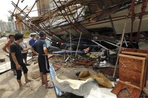 In this July 19, 2014 photo released by China's Xinhua News Agency, a vehicle sits under a collapsed building after landfall of typhoon Rammasun in Haikou, capital of south China's Hainan Province.