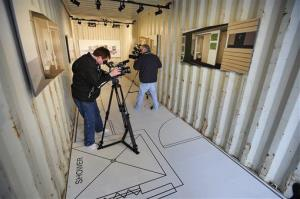 Members of the media film the interior of a cargo container with a blueprint of a two-bedroom homestead in Detroit, resembling the container homes being built in DC.