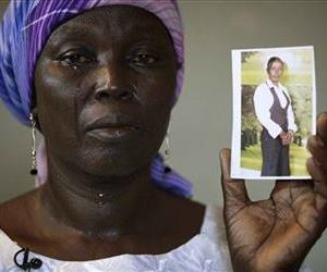 FILE-In this Monday, May 19, 2014 file photo, Martha Mark, the mother of kidnapped school girl Monica Mark cries as she displays her photo, in the family house, in Chibok, Nigeria. At least 11 parents of the more than 200 kidnapped Nigerian schoolgirls will never see their daughters again. Since...