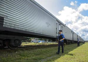 Police officers secure a refrigerated train loaded with bodies of the passengers as it arrives in the Kharkiv railway station Tuesday.