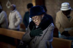 A black woman prays in church. Her biological age is on average three years higher than that of similarly situated whites, according to a new study.