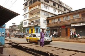 A woman walks near the Arwa clinic, center rear, in Freetown, Sierra Leone, where the doctor contracted the virus.
