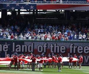 A flag is unfurled in the outfield during the singing of the Star Spangled Banner before a baseball game.