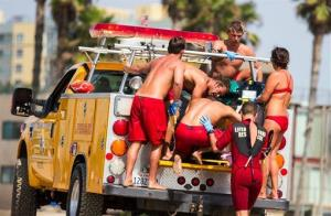 Lifeguards assist a person who was in the water and apparently struck by lightning in Los Angeles yesterday.