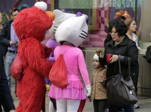 In this April 9, 2013, file photo, a woman prepares to pay characters in New York's Times Square after she photographed a young girl with them.