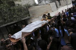 Palestinians carry Gamal Ielian, 10, who was killed along with 9 others, all but one of them children, in an explosion at a park in Gaza Strip, Monday, July 28, 2014.