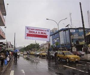 In this photo taken on Monday, July 28, 2014, people hang out in a street under a  banner which warns people to be cautious about Ebola, in Monrovia, Liberia.