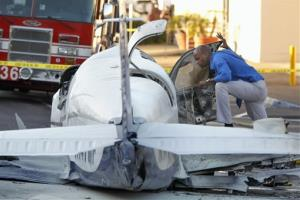 An aviation safety inspector looks inside the cockpit of a small airplane after it crashed in a shopping center parking lot Wednesday afternoon, July 30, 2014, in San Diego. One woman was killed and another seriously injured, a fire spokesman said.