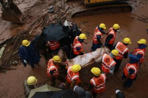 Rescue workers carry the body of a victim after a massive landslide in the village of Malin in India on July 31, 2014.