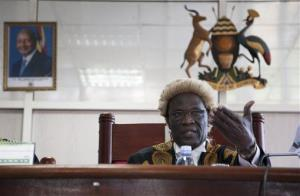 A photo of Uganda's president hangs on the wall, left, as Judge Stephen Kavuma reads the verdict  at Uganda's Constitutional court.