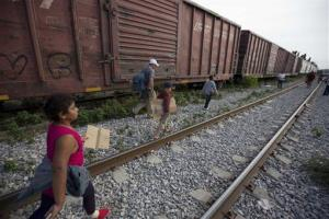 In this July 12, 2014, photo, migrants walk along the rail tracks after getting off a train during their journey toward the US-Mexico border in Ixtepec, Mexico.