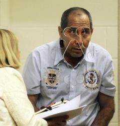 Jose Azurdia-Montenegro, 55, listens from behind a partition to a court interpreter, on Monday, Aug. 4, 2014, in Brockton, Mass., District Court.
