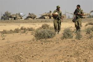 Israeli soldiers walk in a staging area near the Israel Gaza border, Saturday, August 2, 2014.