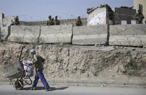 An Afghan laborer walks past a gate of Camp Qargha as Afghanistan National Army soldiers stand guard, west of  Kabul, Afghanistan, Tuesday, Aug. 5, 2014.