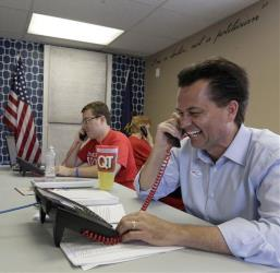 Milton Wolf, right, calls voters at his campaign headquarters yesterday.
