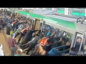People push a Perth train away from the platform to help a man whose leg was stuck in the gap.