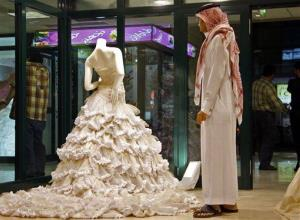 In this file photo, a Saudi man stands in front of a wedding dress at a shop in Riyadh, Saudi Arabia.