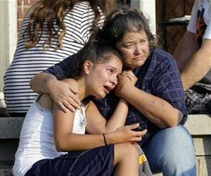 Lisa Kepler, daughter of officer Shannon Kepler, hugs Pam Wilkins on the steps of her home in Tulsa, Okla., on Aug. 6, 2014, the morning after Jeremy Lake was allegedly shot by her Shannon Kepler.