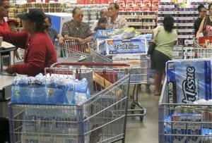 Shoppers stock up on cases of bottled water and other supplies in preparation for a hurricane and tropical storm heading toward Hawaii at the Iwilei Costco in Honolulu on Tuesday, Aug. 5, 2014.
