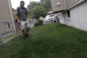 Joseph Perazzo, owner of Grass is Greener Lawn Painting, demonstrates how he sprays lawns in this file photo.