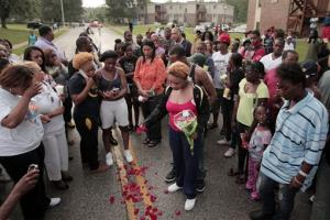 Lesley McSpadden, center, drops rose petals on the blood stains from her 18-year-old son Michael Brown who was shot and killed by police in the middle of the street in Ferguson, Mo., near St. Louis on Saturday, Aug. 9, 2014. McSpadden, told an acquaintance the shooting was wrong and it...