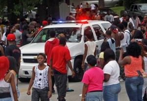 Protesters bang on the side of a police car Sunday evening in Ferguson, Mo.