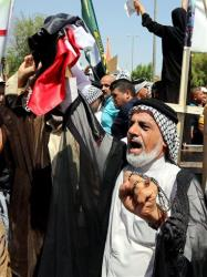 Iraqis chant pro-government slogans and wave national flags to show support for Prime Minister Nouri al-Maliki during a demonstration in Baghdad yesterday.