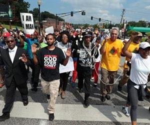 Marchers in downtown Ferguson, Mo., on Monday, Aug. 11, 2014, as they demonstrate at police headquarters against Saturday's police shooting of Michael Brown.