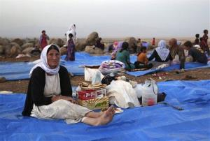 In this Sunday, Aug. 10, 2014, file photo, displaced Iraqis from the Yazidi community settle at a camp in Syria.