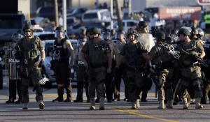 Police in tactical gear stand in a street in Ferguson yesterday.