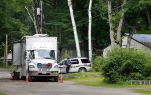 Police stand guard outside the trailer park home of Nathaniel Kibby on Wednesday, Aug. 6, 2014, in Gorham, NH.