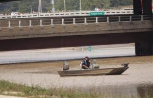 A Michigan State Police officer pilots a boat at the flooded Interstate 75 and I-696 interchange in Hazel Park, Mich., on Aug. 12, 2014, after heavy rains Monday flooded many roadways in the Detroit area.