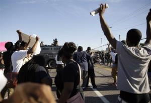 Police in riot gear watch protesters in Ferguson, Mo., on Wednesday.