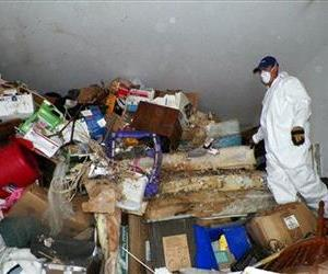 This photo provided by the City of Las Vegas via the Las Vegas Review-Journal shows a worker during a cleanup of hoarder Kenneth Epstein's home in Las Vegas.
