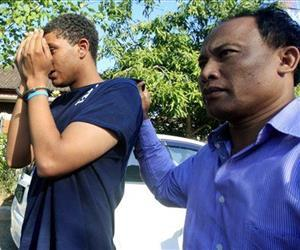 An Indonesian officer escorts Tommy Schaefer, left, as he's brought to the police station for questioning in relation to the death of his girlfriend's mother in Bali, Indonesia, on Aug. 13, 2014.