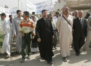 Priest from Assyrian church Tomas Hanna Chamoun, center, and Leader of Awaking Council in southern Baghdad Moustafa al- Jibouri, second right, lead a demonstration in Baghdad, Iraq, on Oct 15, 2008.