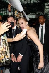 In this May 10, 2014 photo released by Starpix, Jennifer Lawrence, center, and Nicholas Hoult, left, mug for a fans' mobile phone cameras at the premiere of X-Men: Days of Future Past, in New York.