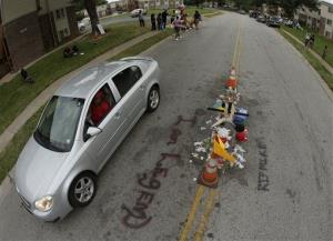 A car drives past a memorial in the middle of the street, Friday, Aug. 15, 2014, where Michael Brown was shot by police nearly a week ago in Ferguson, Mo.