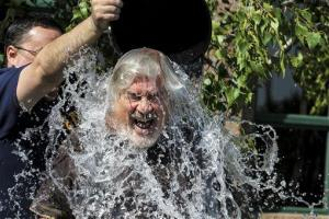 A Florida man reacts as his son pours ice cold water on him, also known as the Ice Bucket Challenge, in Saginaw Township, Mich., Friday, Aug. 15, 2014.