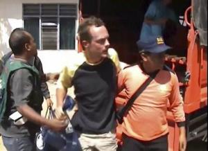 In this image taken from video Sunday, Aug. 17, 2014, a male survivor is escorted to a clinic by rescue team in Lombok, Indonesia, after a boat sank Saturday evening on its way from Lombok island to Komodo island.  Rescuers on Monday safely recovered 13 more people from the tourist...