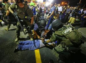 Police handcuff a protester after rushing the crowd to arrest him on West Florissant Avenue in Ferguson early this morning.