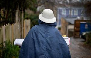A US Postal Service letter carrier delivers mail in the rain in this 2013 file photo.