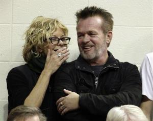Actress Meg Ryan, left, talks with performer John Mellencamp during the second half of an NCAA college basketball game between Indiana and Ohio State, Saturday, Dec. 31, 2011, in Bloomington, Ind.