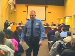 In this  Feb. 11, 2014 image from video released by the City of Ferguson, Mo., officer Darren Wilson attends a city council meeting in Ferguson.
