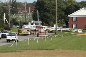 A Campbellsville Fire Department truck with the ladder extended remained at the scene on Thursday, Aug. 21, 2014, in Campbellsville, Ky.