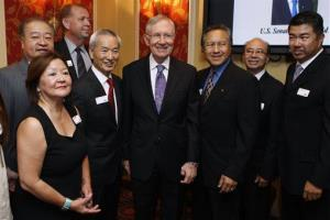 Harry Reid, center, takes photographs with members of the Asian Chamber of Commerce.
